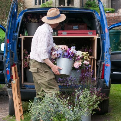 A van full of buckets of flowers
